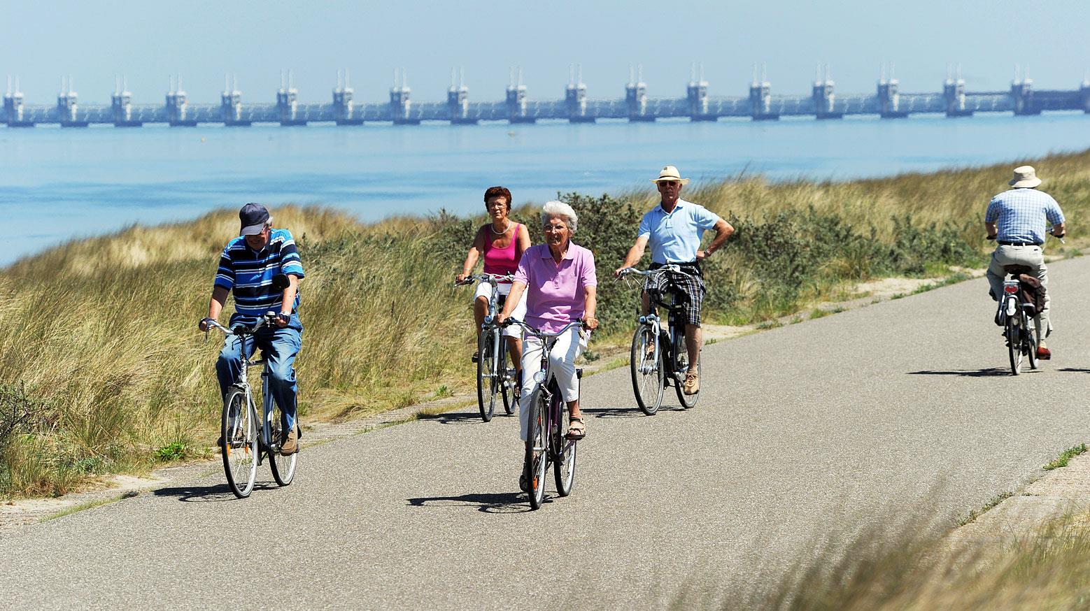 Mensen fietsen in Zeeland langs het water.
