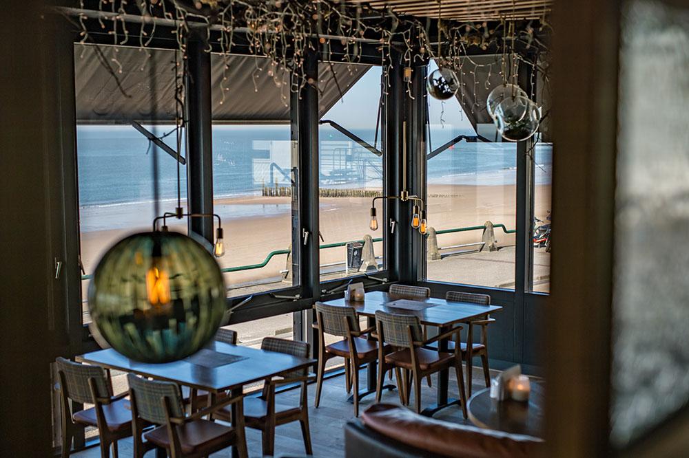 Interieur met uitzicht op het strand in Grand Café Next in Vlissingen.